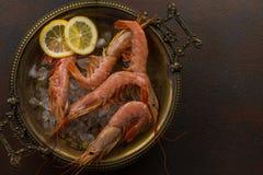 大老虎虾用柠檬和冰块在古老板材在黑暗的石背景 在开胃海鲜快餐的顶视图 库存照片