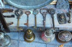 大老钥匙、马掌和金属盘在一家古董店的柜台 免版税库存图片