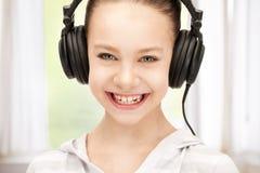 大耳机的愉快的十几岁的女孩 免版税库存照片