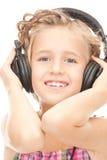 大耳机的愉快的女孩 免版税库存图片