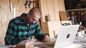 大胆与髭年轻木匠工匠在他的木车间做与膝上型计算机的图画 影视素材