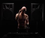 大胆的成人DJ站立在两位大报告人之间的近的搅拌器半赤裸与白色耳机和太阳镜 免版税库存照片