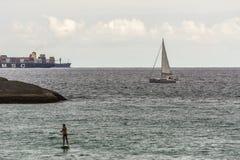 大船,帆船和站立桨冲浪者在科帕卡瓦纳,里约热内卢,巴西 免版税图库摄影