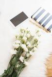 大花束白花、笔记本和片剂在地板上在一张白色毛皮地毯 舒适,时尚舒适的阴物家 库存照片