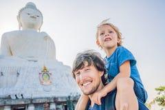 大菩萨雕象的父亲和儿子游人 在普吉岛泰国一个高小山顶被修造了能从远方被看见 库存照片