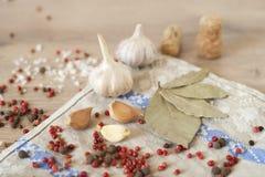 大蒜、月桂树和红辣椒在木背景 库存照片