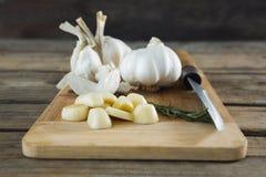 大蒜、迷迭香和刀子在砧板 免版税库存图片