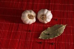 大蒜、黑胡椒和月桂叶在红色背景 免版税库存图片