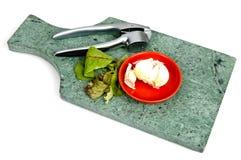 大蒜和大蒜压榨机在一个大理石切板 免版税库存照片