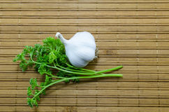 大蒜和荷兰芹在一张竹桌布 图库摄影