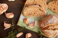大蒜和面包的构成在一张黑暗的木桌上 在洗碗布的新近地被烘烤的手工制造面包 面包被切成切片 免版税图库摄影