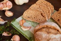 大蒜和面包的构成在一张黑暗的木桌上 在洗碗布的新近地被烘烤的手工制造面包 面包被切成切片 免版税库存图片