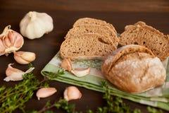 大蒜和面包的构成在一张黑暗的木桌上 在洗碗布的新近地被烘烤的手工制造面包 面包被切成切片 免版税库存照片