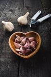 大蒜在一张木黑桌上的 与铁大蒜压榨机的新鲜的大蒜电灯泡 背景几何老装饰品纸张葡萄酒 农夫 医学和healt 免版税图库摄影