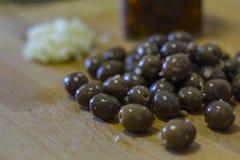 大蒜在木板的用卤汁泡的橄榄 免版税库存图片