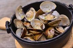 大蒜在黑罐的白葡萄酒蛤蜊在亚洲休息的木盘子 库存照片