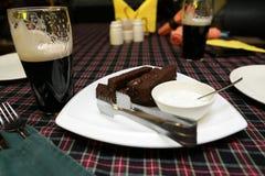 大蒜油煎方型小面包片和黑啤酒杯子 免版税库存图片