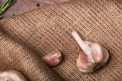 大蒜电灯泡 在棕色背景的白色大蒜 切在粗麻布大袋的削皮的大蒜 健康菜和香料 库存照片