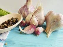大蒜,烹调生气勃勃厨房在蓝色木头的黑胡椒有机葡萄酒调味料芳香营养菜 免版税库存图片
