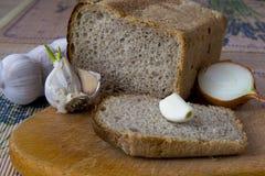 大蒜,葱,在桌上的面包 免版税库存图片