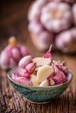 大蒜 在老木板的新鲜的大蒜电灯泡 红色紫罗兰色大蒜 免版税库存照片