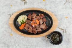 大蒜Saikoro牛排顶视图:半生半熟模子wagyu顶部与剁碎在热板的红萝卜服务用土豆沙拉 库存照片