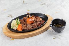 大蒜Saikoro牛排顶视图:半生半熟模子wagyu顶部与剁碎在热板的红萝卜服务用土豆沙拉 免版税图库摄影