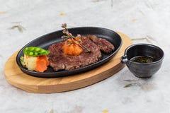 大蒜Saikoro牛排顶视图:半生半熟模子wagyu顶部与剁碎在热板的红萝卜服务用土豆沙拉 库存图片