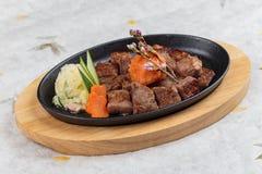 大蒜Saikoro牛排:半生半熟模子wagyu顶部与剁碎在热板的红萝卜服务用土豆沙拉 免版税库存图片