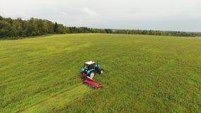大蓝色拖拉机慢慢地割与长方形红色刈草机的领域表面 影视素材