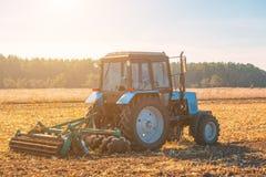 大蓝色拖拉机犁在收获在晴朗的玉米庄稼以后犁了土地,清楚,秋天天 免版税图库摄影