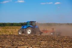 大蓝色拖拉机犁领域并且去除以前被割的向日葵遗骸  库存照片