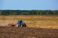 大蓝色拖拉机犁领域并且去除以前被割的向日葵遗骸  免版税库存图片