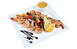 大虾烤了与在方形的陶瓷大盘子iso的菜 免版税库存图片