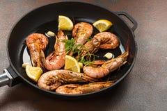 大虾虾用大蒜、柠檬、香料和意大利欧芹在白色被绘的土气木头,选择的焦点的一个黑平底锅装饰, 免版税库存图片