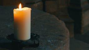 大蜡白色蜡烛烧伤和立场在一个老烛台在一个老中世纪教会里在德国 影视素材