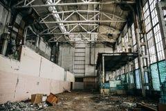 大蠕动的被放弃的工业仓库或工厂大厦里面与从大块玻璃的残破的被破坏的墙壁 免版税图库摄影