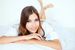 大衬衣的美丽的少妇在床上 免版税库存照片