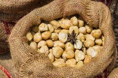 大袋在木背景的干泰国豆蔻果实 库存照片