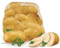 大袋用未加工的土豆和荷兰芹叶子 免版税图库摄影