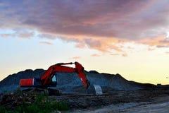 大被跟踪的挖掘机在采石坑运转反对日落和惊人的天空 免版税图库摄影