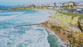 大西洋海岸和冲浪者鸟瞰图在水中在波浪在卡斯卡伊斯,葡萄牙 Clifs海岸和海 股票录像