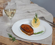 大西洋三文鱼内圆角,用柠檬、迷迭香和杯在一张木桌上的白葡萄酒 库存图片