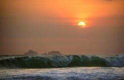 大西洋大波浪Ipanema海滩和美好的日落的与云彩和橙色天空,里约热内卢 库存照片
