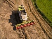 大角度在收获麦子的看法现代联合收割机 免版税库存图片