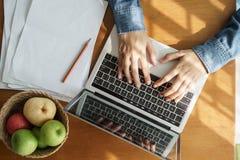 大角度看法显示妇女的手在膝上型计算机键入 哪些食用在桌上和果子把放的纸在太阳发光 免版税库存图片