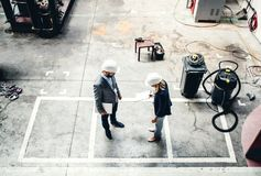 大角度观点的一位工业男人和妇女工程师在工厂 免版税库存照片