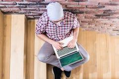 大角度观点的使用膝上型计算机的时兴的人,当坐在办公楼时的台阶 免版税库存照片