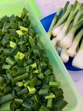 大角度观点的在一个绿色塑料盒的新鲜的切的春天葱 库存照片