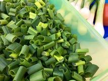 大角度观点的在一个绿色塑料盒的新鲜的切的春天葱 免版税库存照片